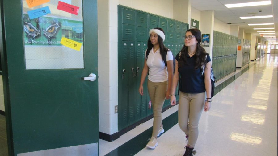 Eighth graders, Briana Worthington and Mercedes Storey walk to their classes in consideration of the late policy.