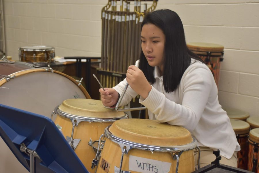 Juarez enjoys playing percussion in the school band. Here, she plays the triangle while reading music.