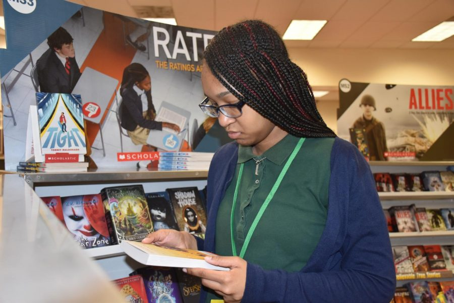 8th grader, Lisaraye Horne reads the back of a book in interest.