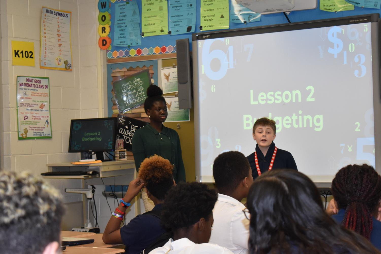 Olamide Daodu and Isaac Moran with their slideshow to teach seventh graders budgeting basics.
