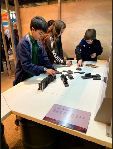 Ethan Mandap, Faith Kennedy, and Thomas Rotenbury explore the concepts of physics with dominoes at The Franklin Institute.