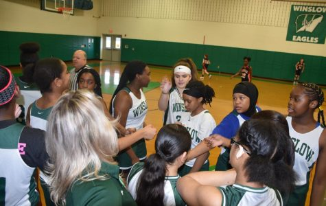 The team throws hands in for a cheer before going back out to take the court,