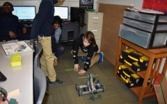 Members of the team test the robot to see if they can identify way to improve on their engineering design plan.